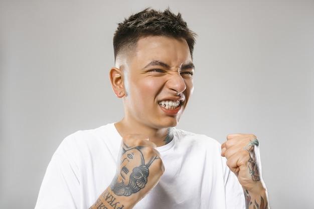 Der junge emotionale böse mann, der auf grauer studiowand schreit