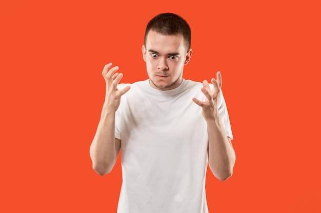 Der junge emotionale verärgerte mann auf orange raum