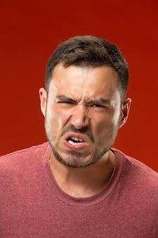 Der junge emotionale verärgerte mann, der auf rote studiowand schreit