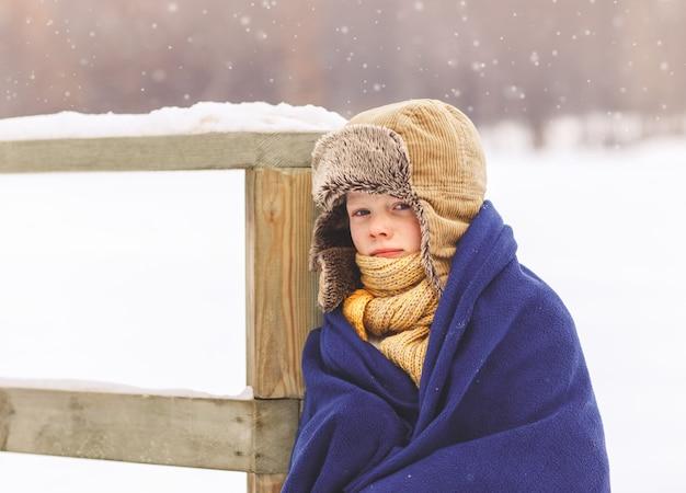 Der junge erstarrte im winter und wickelte sich im winter im park in eine decke
