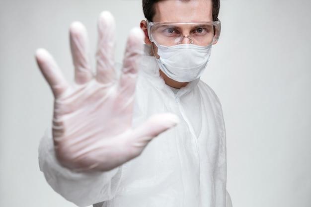 Der junge europäische arzt im virenschutzanzug zeigt eine handbewegung, um die coronavirus- oder covid-19-epidemie zu stoppen