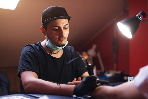 Der junge, fokussierte tätowierer färbt die kunden in seinem geschäft sorgfältig ein.