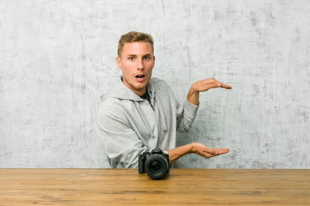 Der junge fotograf, der eine kamera auf einer tabelle hält, entsetzte und überraschte das halten eines kopienraumes zwischen händen.