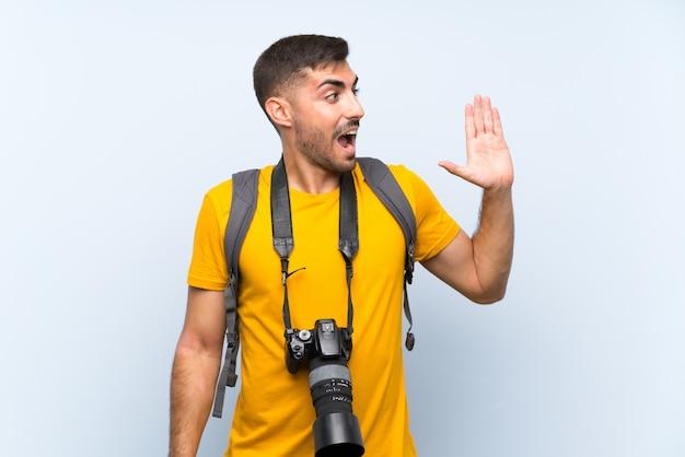 Der junge fotografmann, der mit dem breiten mund schreit, öffnen sich