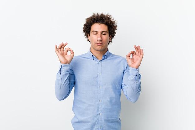 Der junge gelockte reife mann, der ein elegantes hemd trägt, entspannt sich nach hartem arbeitstag, sie führt yoga durch.