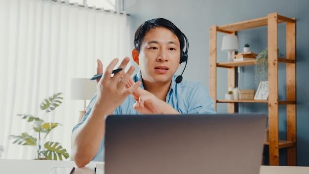 Der junge geschäftsmann aus asien trägt kopfhörer mit einem laptop. sprechen sie mit kollegen über den plan eines videoanrufs, während sie von zu hause aus im wohnzimmer arbeiten.