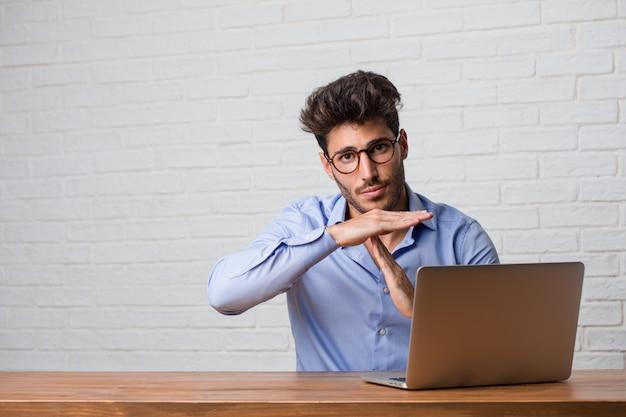 Der junge geschäftsmann, der an einem laptop sitzt und arbeitet, der müde und gelangweilt ist und eine auszeitgeste macht, muss wegen des arbeitsstresses, zeitkonzept aufhören