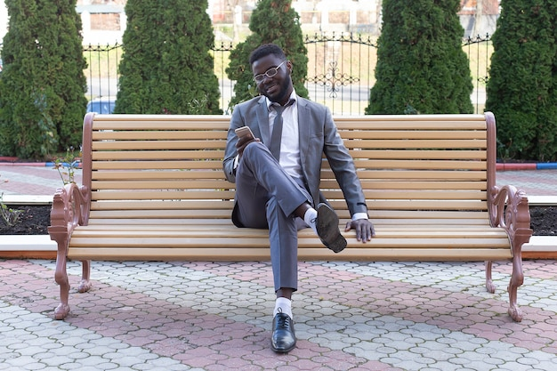 Der junge geschäftsmann, der auf stadtbank mit telefon lächelt