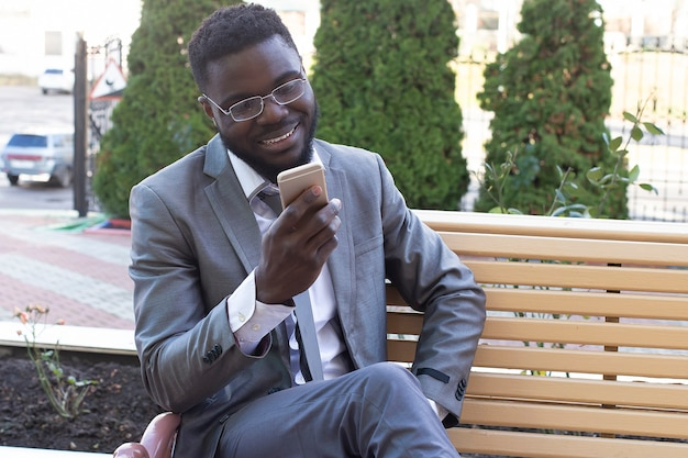 Der junge geschäftsmann, der auf stadtbank mit telefon, tablette lächelt