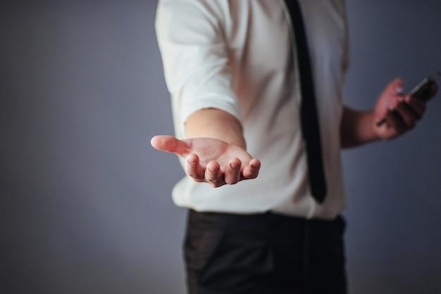 Der junge geschäftsmann, der leere hände zeigt, bereiten vor, um mit ihrem design zu füllen
