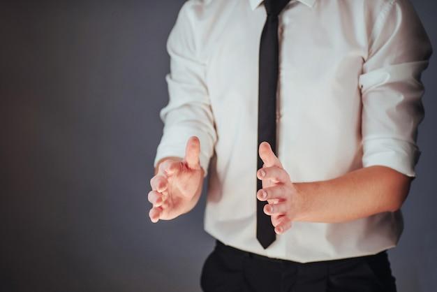 Der junge geschäftsmann in einer klage zeigt seine hand auf einem dunklen lokalisierten hintergrund