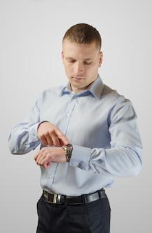 Der junge geschäftsmann zeigt auf seine uhr am arm. auf weißer oberfläche isoliert.