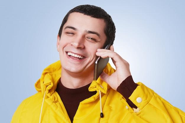 Der junge glückliche gutaussehende mann hat ein telefongespräch, spricht mit dem besten freund, bespricht etwas mit fröhlichem ausdruck, freut sich, ihn zu hören, trägt einen gelben anorak, der über blau isoliert ist. technologiekonzept