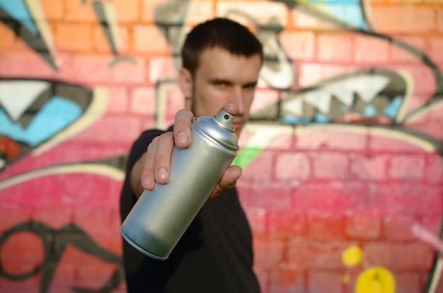 Der junge graffiti-künstler zielt auf sein spray