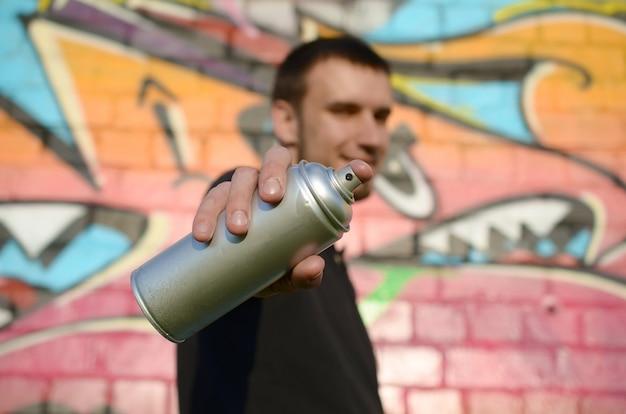Der junge graffiti-künstler zielt auf seine spraydose