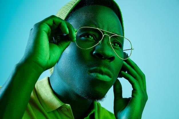 Der junge gutaussehende ernsthafte traurige hipster-mann, der musik mit kopfhörern an mit neonlichtern hört