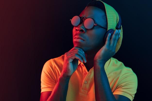Der junge gutaussehende ernsthafte traurige hipster-mann, der musik mit kopfhörern im schwarzen studio mit neonlichtern hört