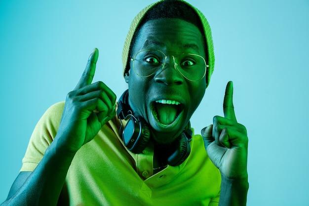 Der junge gutaussehende glücklich überraschte hipster-mann, der musik hört