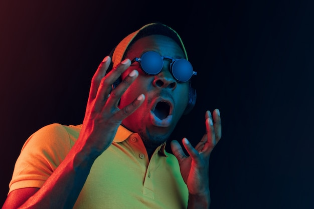 Der junge gutaussehende glückliche überraschte hipster-mann, der musik mit kopfhörern im schwarzen studio mit neonlichtern hört. disco, nachtclub, hip-hop-stil, positive emotionen, gesichtsausdruck, tanzkonzept
