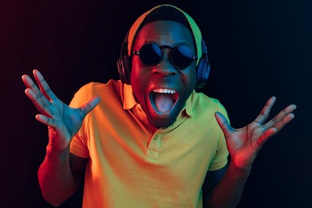 Der junge gutaussehende glückliche überraschte hipster-mann, der musik mit kopfhörern im schwarzen studio mit neonlichtern hört.