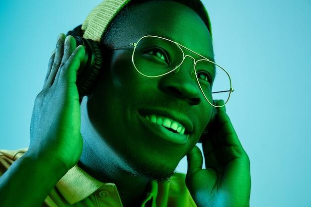 Der junge gutaussehende glückliche überraschte hipster-mann, der musik mit kopfhörern im studio mit neonlichtern hört. disco, nachtclub, hip-hop-stil, positive emotionen, gesichtsausdruck, tanzkonzept