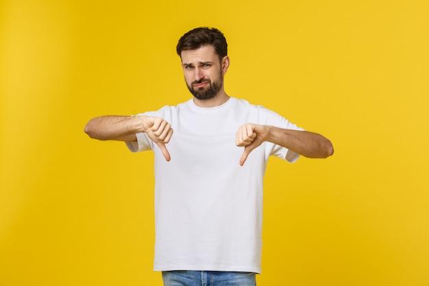 Der junge gutaussehende mann, der daumen unten tuend trägt, unterzeichnen mit den händen, widerspruchsausdruck.