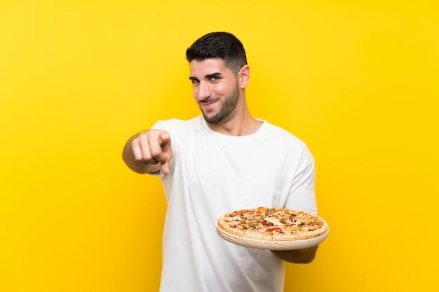 Der junge gutaussehende mann, der eine pizza über lokalisierter gelber wand hält, zeigt finger auf sie mit einem überzeugten ausdruck