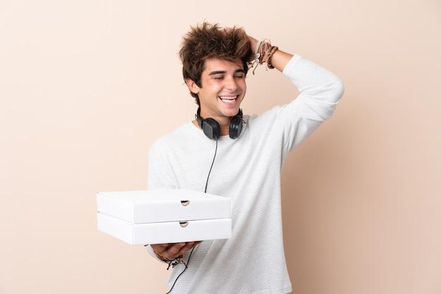 Der junge gutaussehende mann, der eine pizza über lokalisierter wand hält, hat etwas verwirklicht und die lösung beabsichtigt