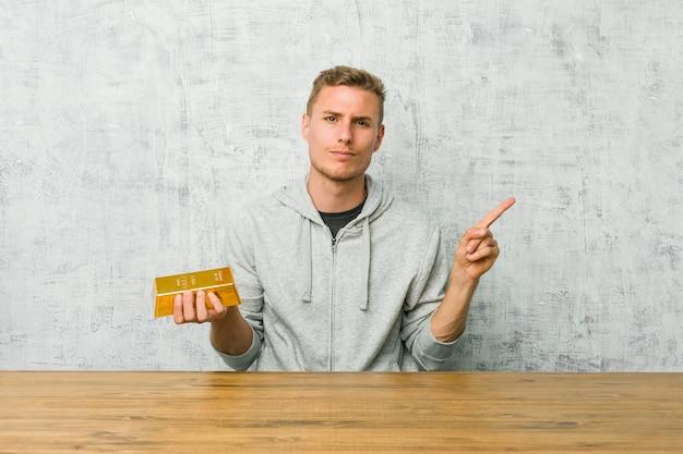 Der junge gutaussehende mann, der einen goldbarren auf einer tabelle hält, zeigt seitlich, versucht, zwischen zwei wahlen zu wählen.