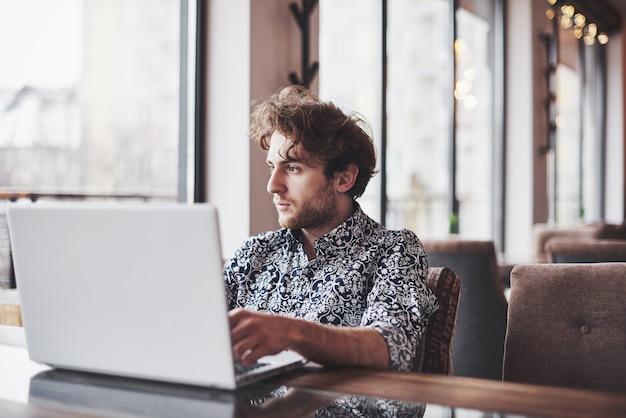 Der junge gutaussehende mann, der im büro mit tasse kaffee sitzt und an projekt arbeitet, schloss an moderne cybertechnologien an. geschäftsmann mit dem notizbuch, das versucht, frist im bereich des digitalen marketings zu halten