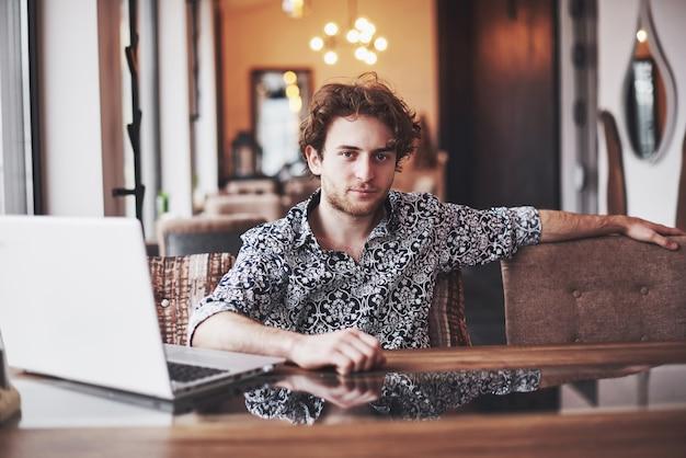 Der junge gutaussehende mann, der im büro mit tasse kaffee sitzt und an projekt arbeitet, schloss an moderne cybertechnologien an