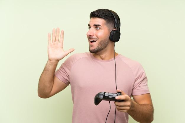 Der junge gutaussehende mann, der mit einem videospielprüfer auf der grünen wand schreit mit dem breiten mund spielt, öffnen sich