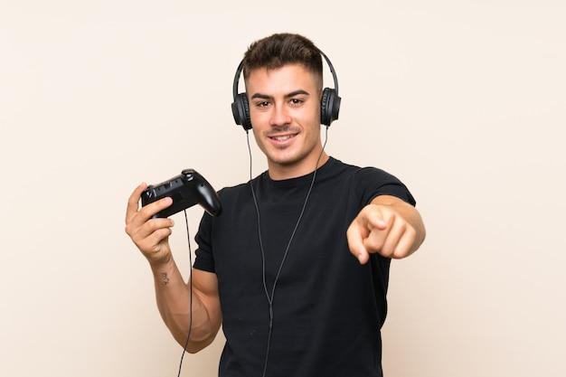 Der junge gutaussehende mann, der mit einem videospielprüfer über lokalisierter wand spielt, zeigt finger auf sie mit einem überzeugten ausdruck