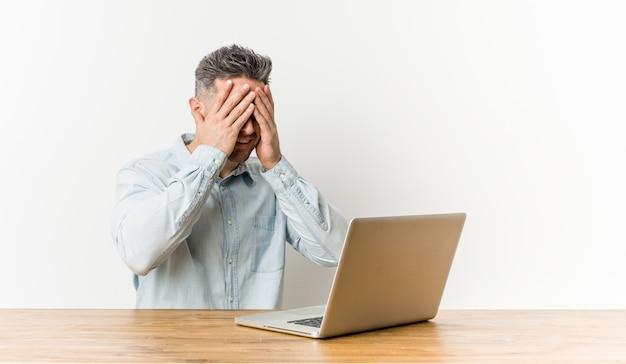 Der junge gutaussehende mann, der mit seinem laptop arbeitet, bedeckt augen mit den händen und lächelt breit, auf eine überraschung wartend.
