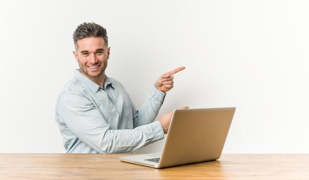 Der junge gutaussehende mann, der mit seinem laptop arbeitet, regte das zeigen mit den zeigefingern weg auf.