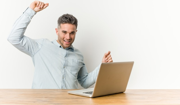 Der junge gutaussehende mann, der mit seinem laptop feiert einen speziellen tag arbeitet, springt und hebt arme mit energie an.