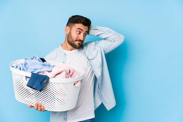 Der junge gutaussehende mann, der wäscherei tut, lokalisierte das berühren zurück vom kopf, dachte und traf eine wahl.
