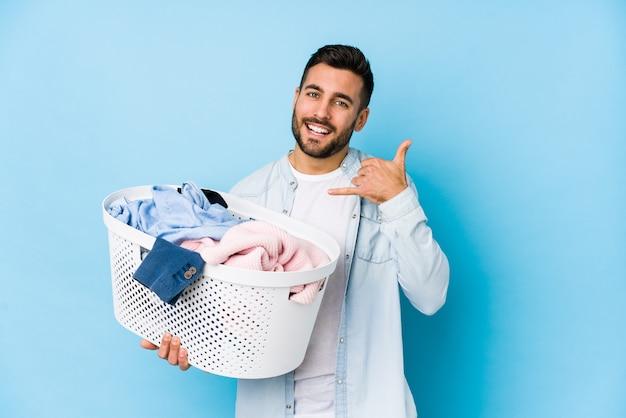 Der junge gutaussehende mann, der wäscherei tut, lokalisierte das zeigen einer handyanrufgeste mit den fingern.
