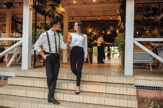 Der junge, gutaussehende mann hilft der frau, die treppe des sommerterrassencafés hinunterzugehen