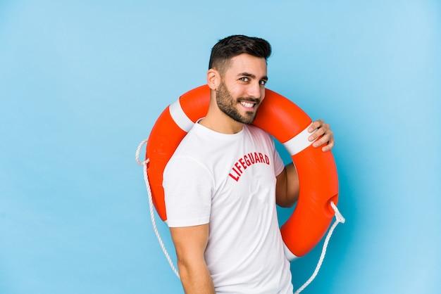 Der junge, gutaussehende rettungsschwimmer sieht isoalted lächelnd, fröhlich und angenehm aus.