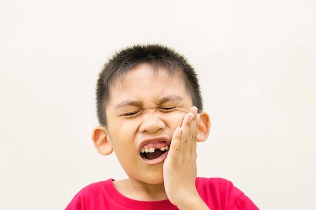 Der junge hält seine hand auf seiner wange und rotem gesicht mit schmerz von zahnweh.