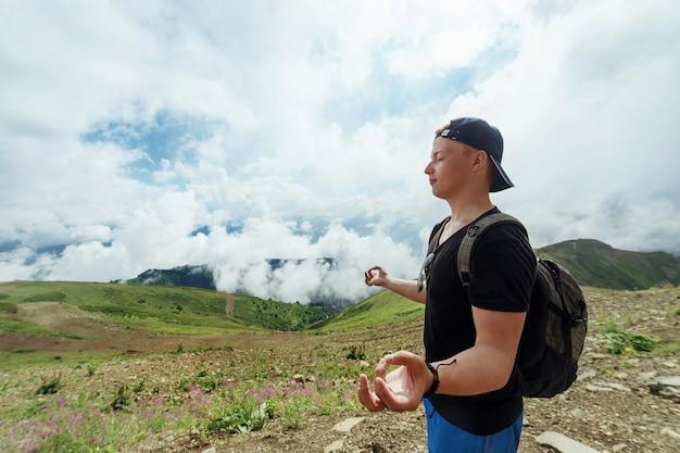 Der junge hipster-mann meditiert gegen die berge in wolken