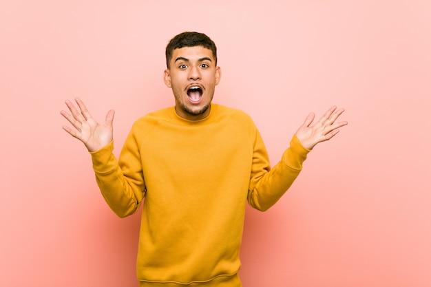 Der junge hispanische mann, der einen sieg oder einen erfolg feiert, ist er überrascht und entsetzt.