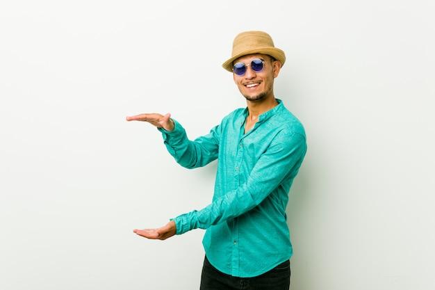 Der junge hispanische mann, der einen sommer trägt, kleidet das entsetzte und überraschte halten eines kopienraumes zwischen händen.