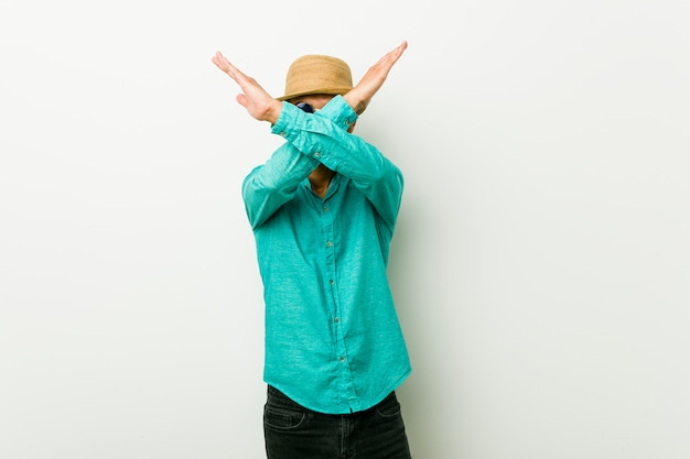 Der junge hispanische mann, der einen sommer trägt, kleidet das halten von zwei armen gekreuzt, ablehnungskonzept.