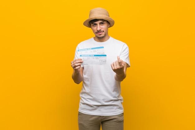 Der junge hispanische mann, halten flugtickets, die mit dem finger auf sie zeigen, als ob einladung näher kommen.