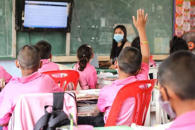 Der junge hob die hand, um den lehrer im klassenzimmer zu fragen