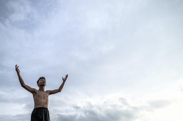 Der junge hob die hand zum himmel, um nach regen, globaler erwärmung und wasserkrise zu fragen
