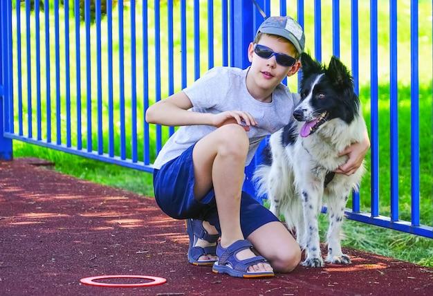 Der junge hockt neben dem hund.