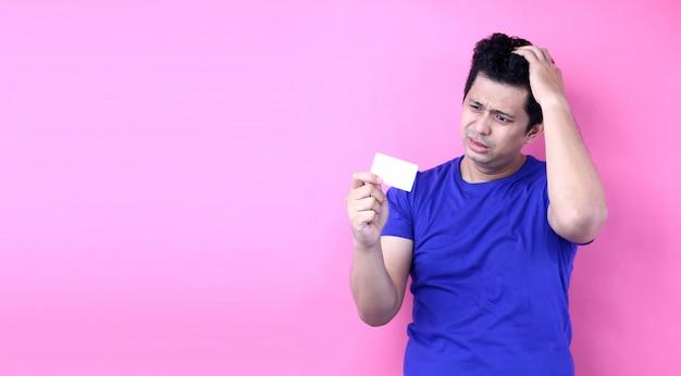 Der junge hübsche asien-mann, der kreditkartenraum hält, erschrak im schock mit einem überraschungsgesicht, ängstlich und aufgeregt mit furchtausdruck auf rosa hintergrund im studio